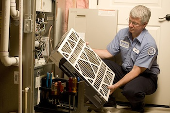 A technician inspects the air filter from a furnace
