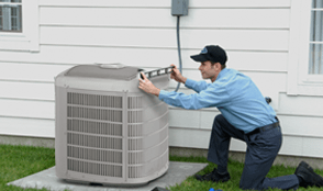 A technician checking if an outdoor air conditioning unit is level