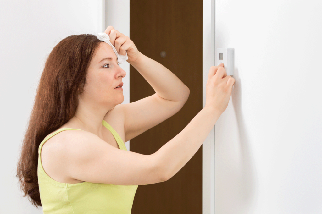 Woman sweating and checking thermostat